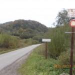 Z prawej tabliczka rezerwatu, z lewej ambona, w środku droga leśna